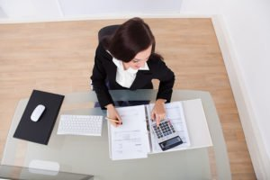 Happy Businesswoman Calculating Tax